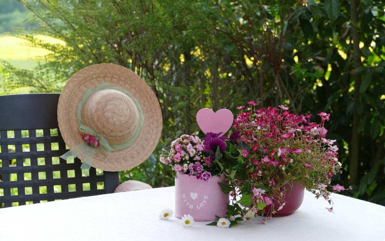 Pots de fleurs posés sur la table avec un chapeau sur la chaise, hôtel 4 étoiles provence, Hôtel de L'Image.